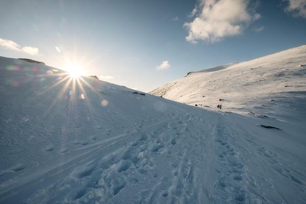 Zachód słońca na zaśnieżonym wzgórzu z alpinistami i odciskiem stopy na górze ryten, lofoty