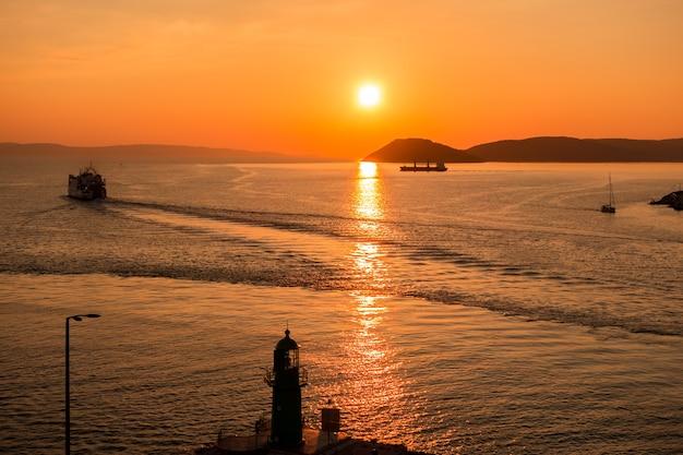 Zachód słońca nad adriatykiem i jego łodzie w odbiciach przy wejściu do portu w splicie w chorwacji.