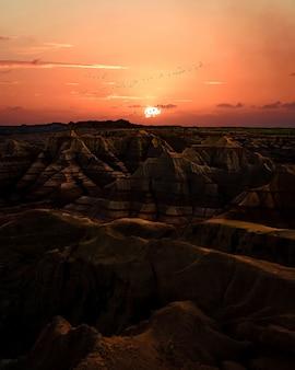 Zachód słońca nad badlands. teren z pasiastymi formacjami skalnymi