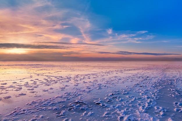 Zachód słońca nad bonneville salt flats kolorowe niebo odbija się w niewielkiej ilości wody deszczowej.