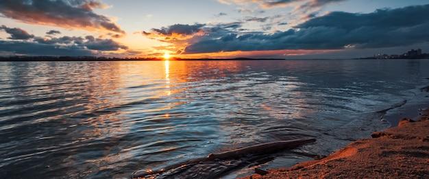 Zachód słońca nad brzegiem rzeki. piękne chmury, błękitna woda gazowana, powalone drzewo w wodzie i piasek na brzegu pomarańczowy z promieni słońca.
