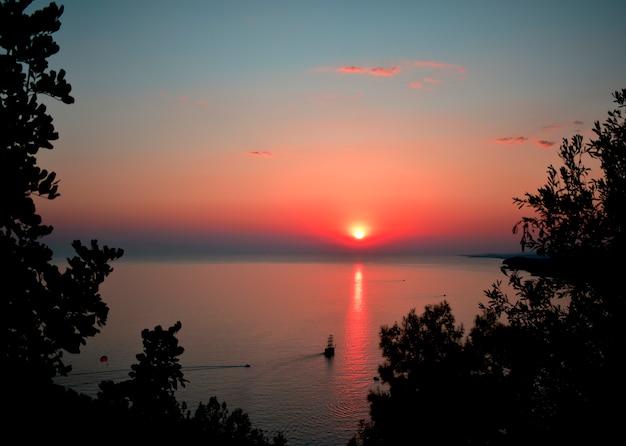 Zachód słońca nad górami i morzem. złota godzina. sylwetka gór i złote niebo oświetlone przez ostatnie promienie słońca.