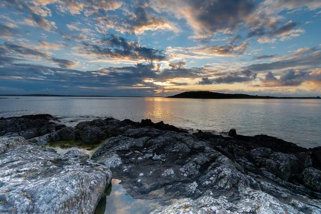 Zachód słońca nad horyzontem oceanu w ciepły wieczór lata w pobliżu nieba drogowego w connemara.