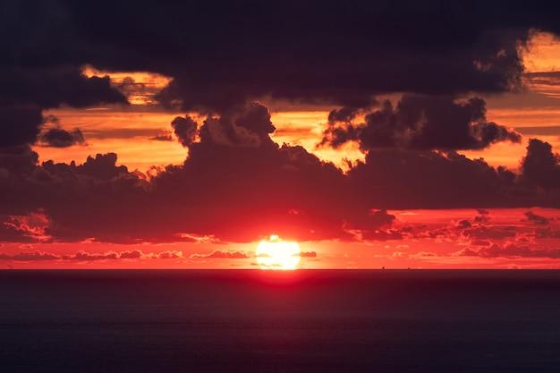 Zachód słońca nad horyzontem w tropikalnym morzu z pochmurnym wieczorem