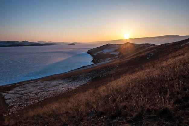 Zachód słońca nad jeziorem bajkał z lodem w zimie