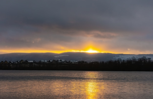 Zachód słońca nad jeziorem w górach sudety zimą