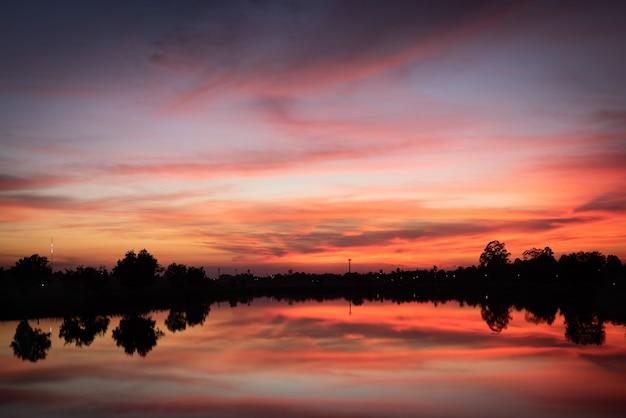 Zachód słońca nad jeziorem z czerwono-pomarańczowym niebem.