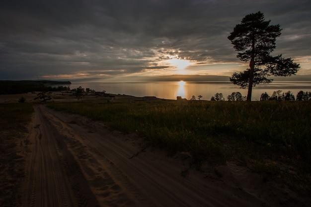 Zachód słońca nad jeziorem z drzewem i piaszczystą drogą. słońce prześwieca przez chmury. słoneczna ścieżka na wodzie.