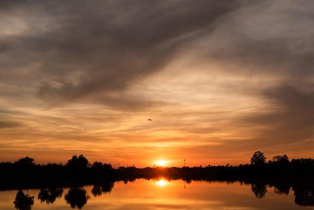 Zachód słońca nad jeziorem z pomarańczowym niebem.