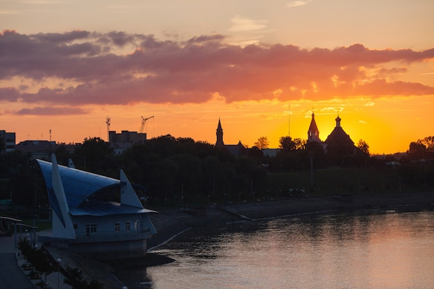Zachód słońca nad katedrą i kościołem, pomarańczowe niebo, chmury, słońce za horyzontem