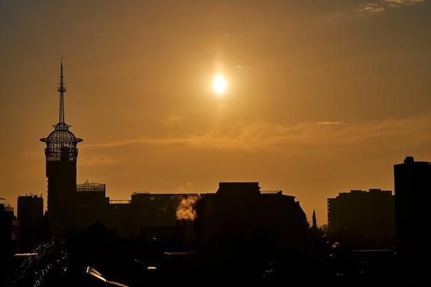 Zachód słońca nad miastem. żółte niebo. sylwetki budynków.