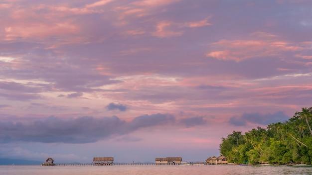 Zachód słońca nad molo stacji nurkowej i homestay na wyspie kri, raja ampat, indonezja, papua zachodnia