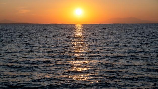 Zachód słońca nad morzem egejskim, słońce, ląd w oddali, woda, grecja