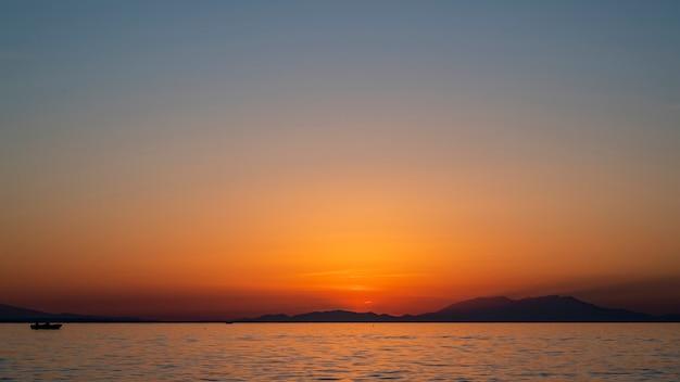 Zachód słońca nad morzem egejskim, statek i ląd w oddali, woda, grecja