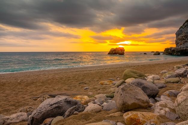 Zachód słońca nad morzem i kamienie na piaszczystej plaży