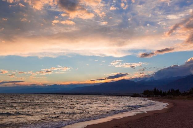 Zachód słońca nad morzem, piękne góry i chmury