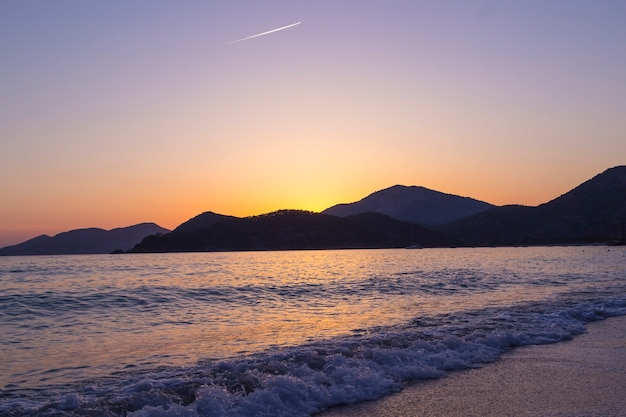 Zachód słońca nad morzem z płynącymi jasnymi kolorowymi promieniami słońca przez chmury
