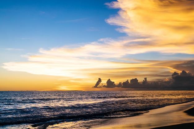Zachód słońca nad oceanem. piękne jasne niebo, odbicie w wodzie, fale.