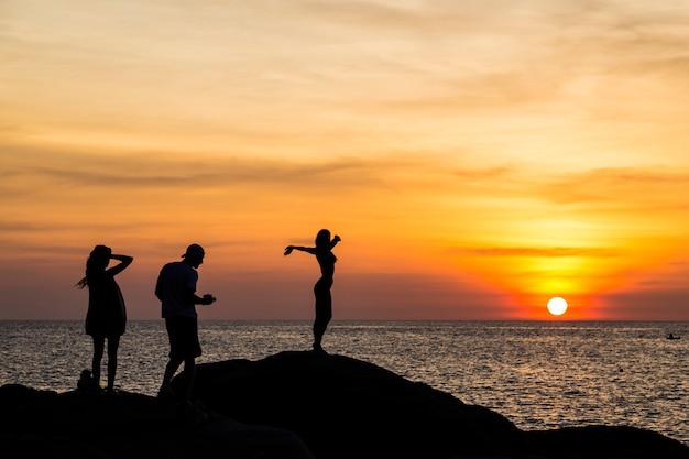 Zachód słońca nad oceanem. sylwetki ludzi na tle zachodzącego słońca