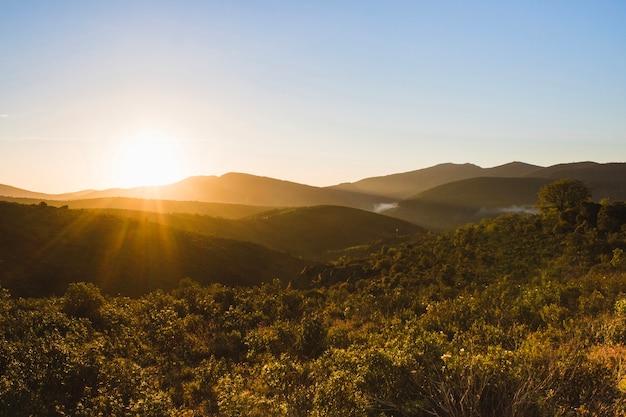Zachód słońca nad pagórkowaty krajobraz