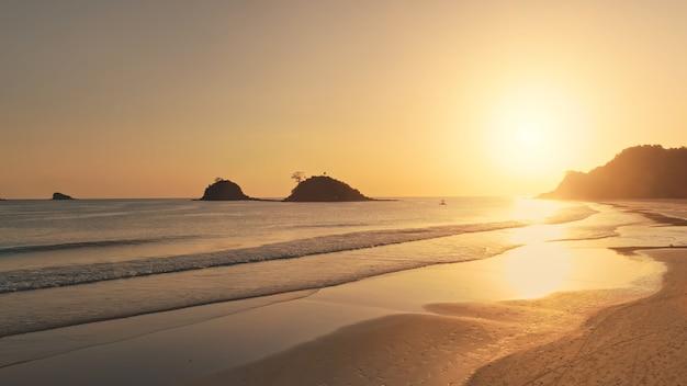 Zachód słońca nad piaszczystą plażą na antenie wybrzeża morskiego. przyroda i krajobraz morski wyspy el nido