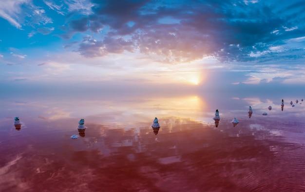 Zachód słońca nad popularnym miejscem turystycznym. różowe słone jezioro ze znacznymi pokładami soli leczniczej na brzegach.