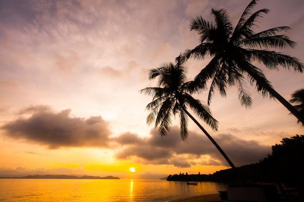 Zachód słońca nad tropikalnym morzem i plażą.