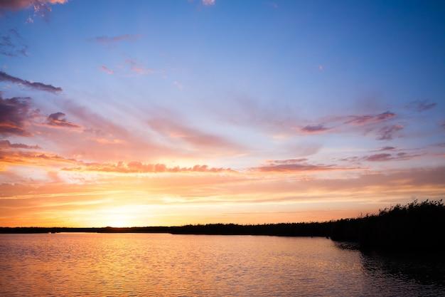 """Zachód słońca nad wodą z """"delta del po"""", włoski krajobraz. woda i niebo"""