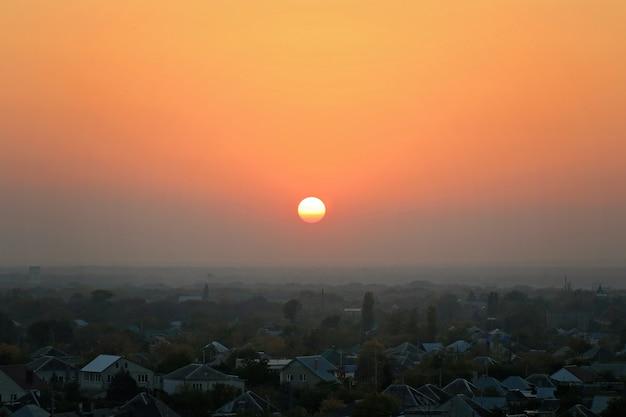 Zachód słońca nad zamglonym miastem, domy. miasto podczas ciepłego zachodu słońca