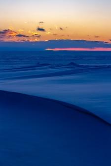 Zachód słońca nad zimowym śnieżnym jeziorem bajkał