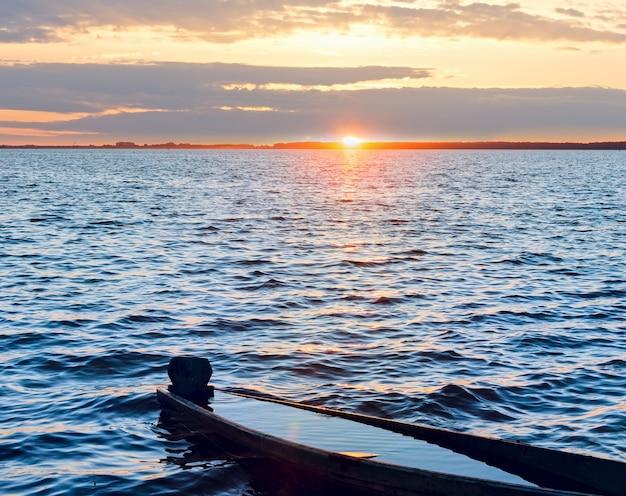 Zachód słońca niebo i stara utopiona drewniana łódź rybacka na brzegu jeziora latem.