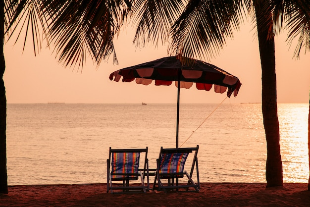 Zachód słońca niebo na plaży z plażą para krzesło i kokosowe drzewo