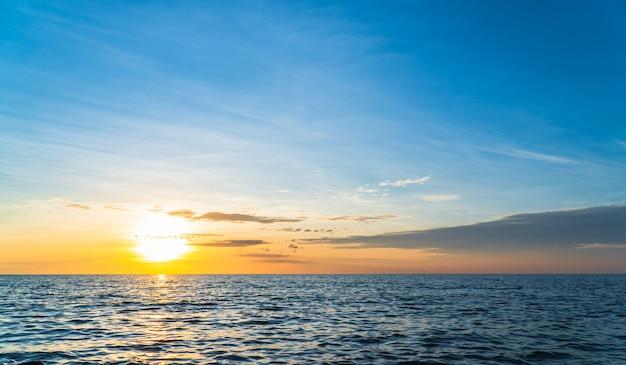 Zachód słońca niebo nad morzem w pionie wieczorem z kolorowym pomarańczowym światłem słonecznym
