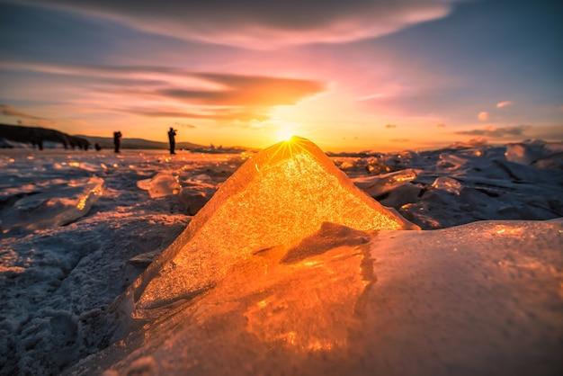 Zachód słońca niebo z naturalnym łamaniem lodu nad zamarzniętą wodą na jeziorze bajkał, syberia, rosja