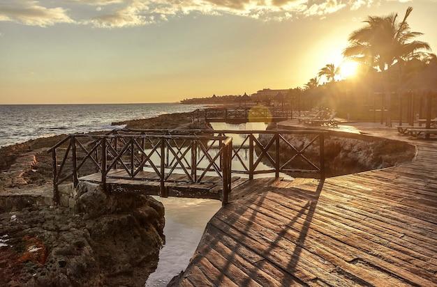 Zachód słońca o zachodzie słońca na drewnianym molo wśród skał na wybrzeżu puerto aventuras w meksyku.