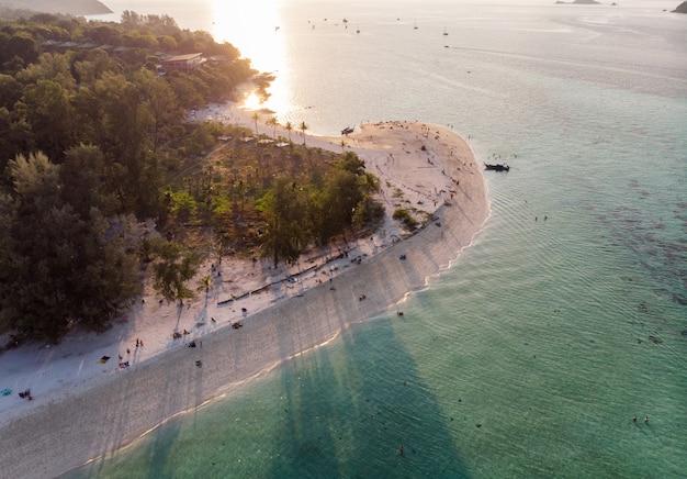 Zachód słońca świeci na białej, piaszczystej plaży z tropikalnym lasem