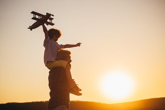 Zachód słońca sylwetka szczęśliwy ojciec i syn dziecka z samolotem marzy o podróżowaniu. ojciec niosący syna na ramionach.