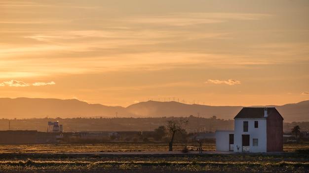 Zachód słońca w albufera w walencji z wiejskim domem.