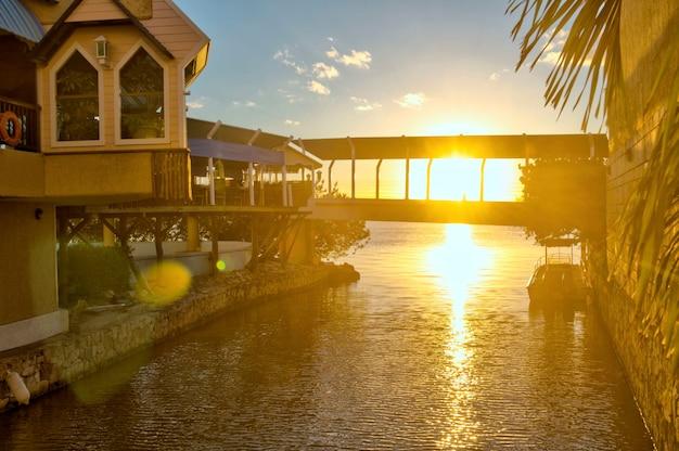 Zachód słońca w centrum handlowym w cancun, quintana roo. piękny widok na wschód słońca na morzu karaibskim. odbicie słońca w spokojnej wodzie