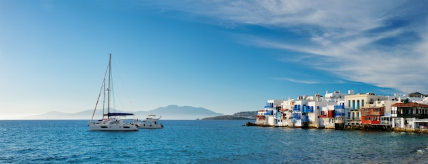 Zachód słońca w grecji mykonos ze statkiem wycieczkowym i jachtami w porcie
