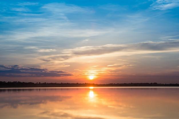 Zachód słońca w jeziorze. piękny zachód słońca za chmurami nad jezioro tle krajobrazu jeziora.