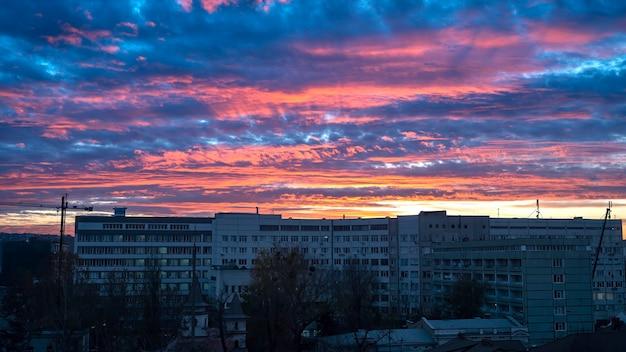 Zachód słońca w kiszyniowie, mołdawia. różowe i niebieskie bujne chmury. na pierwszym planie radzieckie budynki mieszkalne