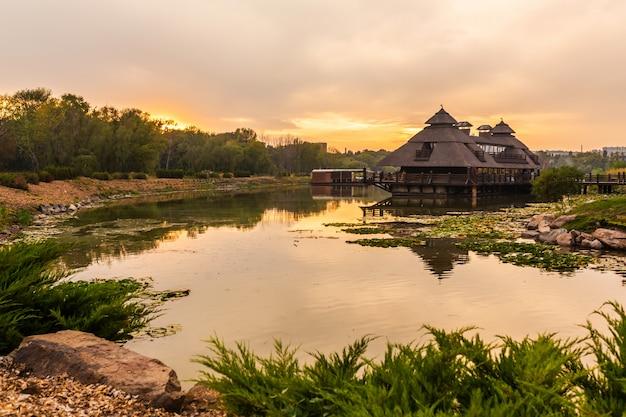 Zachód słońca w malowniczym miejscu. drewniany dom, w pobliżu którego jest jezioro
