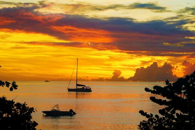 Zachód słońca w morzu i sylwetka jacht żaglowy z pięknym krajobrazem karaibów, wyspy santa lucia