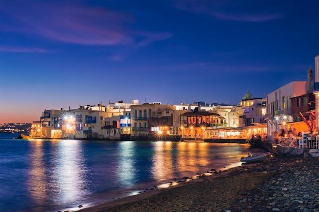 Zachód słońca w mykonos, grecja, ze statkiem wycieczkowym i jachtami w porcie