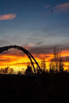 Zachód słońca w śródziemnomorskim mieście z sylwetką metalowej konstrukcji zawieszonego mostu.