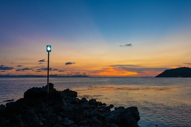 Zachód słońca w tropiku latarnia morska dla łodzi na kamiennym nasypie w pobliżu wybrzeża
