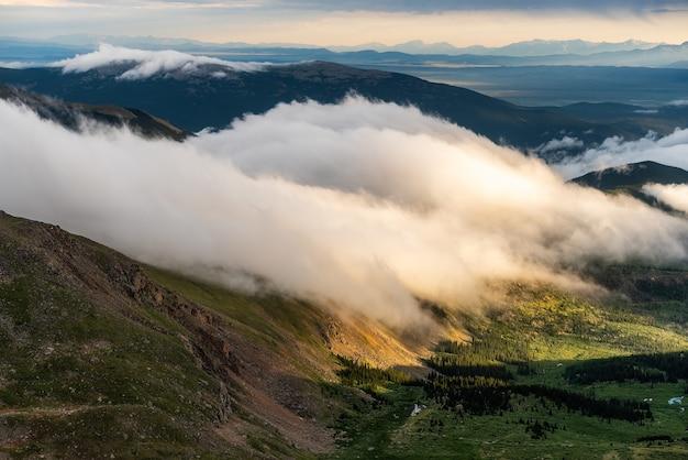 Zachód słońca widok z pasmami górskimi i chmurami