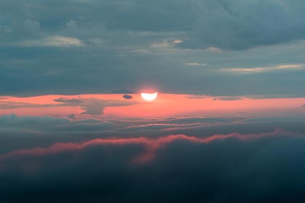 Zachód słońca z czerwonym słońcem i chmurami