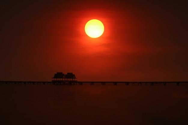 Zachód słońca z powrotem na moście sylwetki i porzuć pawilon na morzu